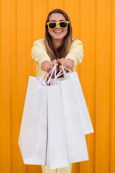 Jeune cliente portant des vêtements jaunes montrant ses sacs à provisions