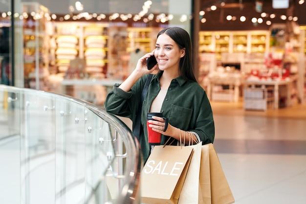 Jeune cliente réussie avec boisson et sacs en papier parlant sur téléphone mobile après avoir visité les départements du grand centre commercial moderne