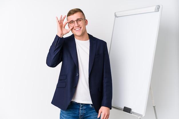 Jeune coaching homme montrant un tableau blanc excité en gardant le geste ok sur les yeux.