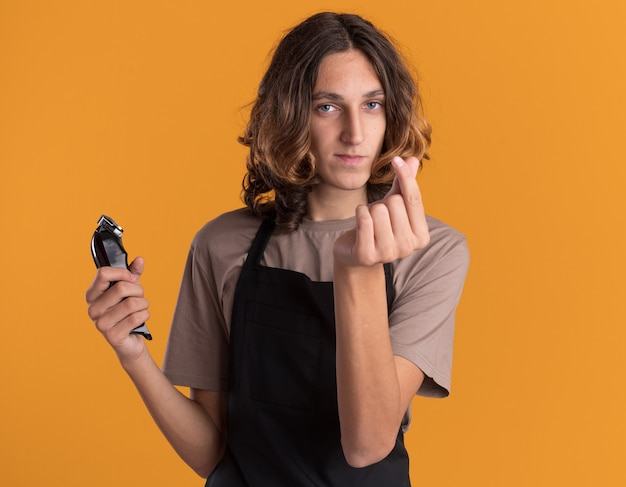Jeune coiffeur beau et confiant en uniforme tenant une tondeuse à cheveux faisant un geste d'argent