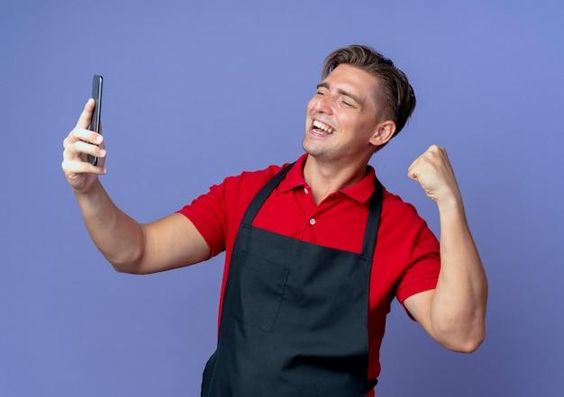 Jeune coiffeur blond souriant en uniforme lève le poing en regardant le téléphone