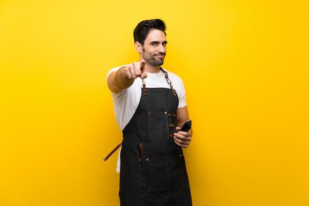 Jeune coiffeur sur fond jaune isolé pointe le doigt vers vous avec une expression confiante
