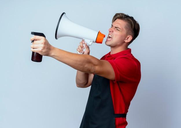 Jeune coiffeur homme blond ennuyé en uniforme détient haut-parleur et vaporisateur isolé sur fond blanc avec espace de copie