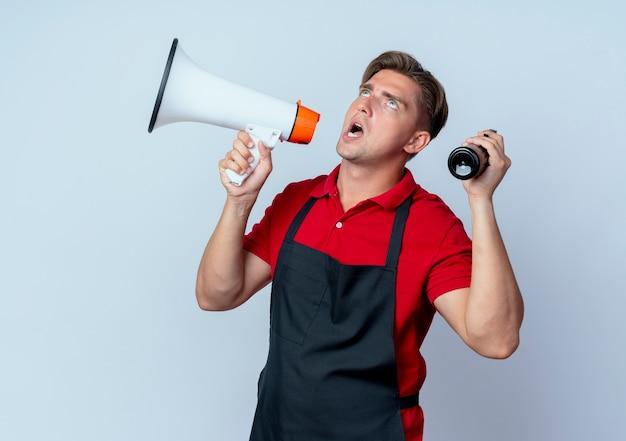 Jeune coiffeur homme blond ennuyé en uniforme détient haut-parleur et vaporisateur à la recherche d'isolement sur l'espace blanc avec copie espace