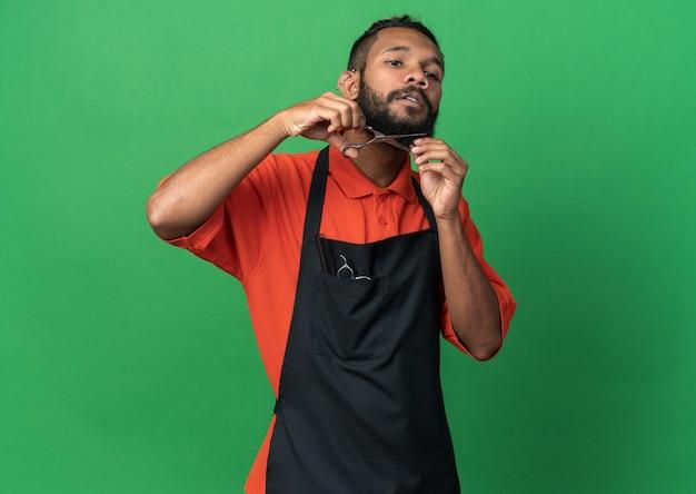 Jeune coiffeur masculin afro-américain concentré en uniforme regardant vers le bas en coupant sa barbe avec des ciseaux