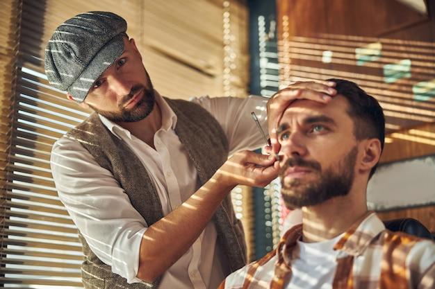 Jeune coiffeur professionnel portant un chapeau cool et rasant son client tout en regardant la caméra