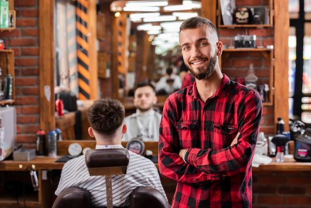 Jeune coiffeuse avec une chemise souriante satisfaite