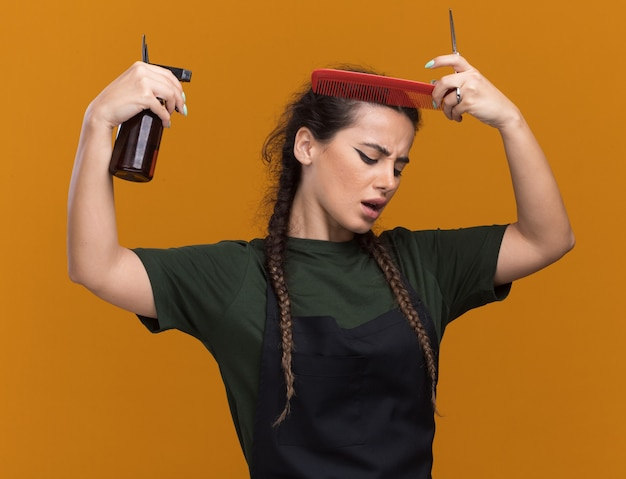 Jeune coiffeuse mécontente en uniforme peignant les cheveux et arrosant la tête avec un vaporisateur isolé sur un mur orange