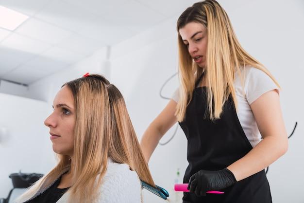 Jeune coiffeuse professionnelle lissage des cheveux d'un client
