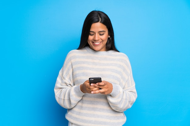 Jeune colombienne avec pull envoie un message avec le portable