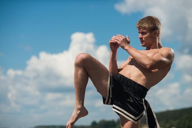 Jeune combattant à coups de pied. exercice en plein air. coup de genou