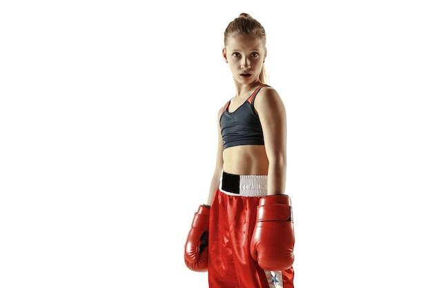 Jeune combattant de kickboxing féminin posant confiant sur fond blanc.