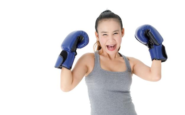 Jeune combattante asiatique victorieuse dans des gants de boxe bleus, levant les mains et souriant joyeusement tout en célébrant le triomphe sur fond blanc