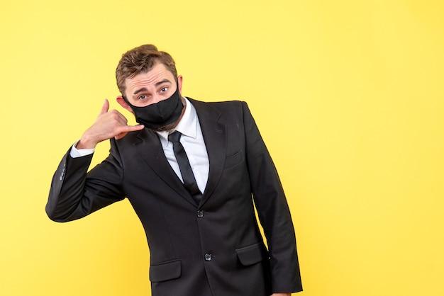 Jeune commerçant avec masque médical montrant le geste de me contacter sur jaune