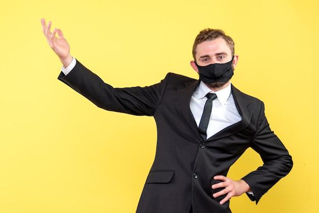 Jeune commerçant portant un masque médical présentant quelque chose sur jaune