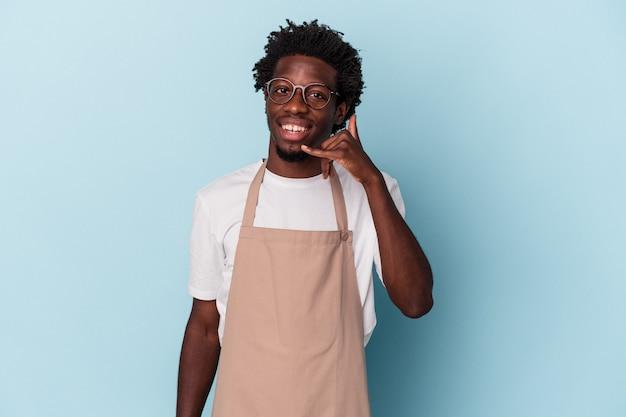 Jeune commis de magasin afro-américain isolé sur fond bleu montrant un geste d'appel de téléphone portable avec les doigts.