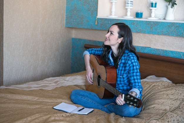 Jeune compositrice compose une chanson à la guitare acoustique sur un lit dans une chambre