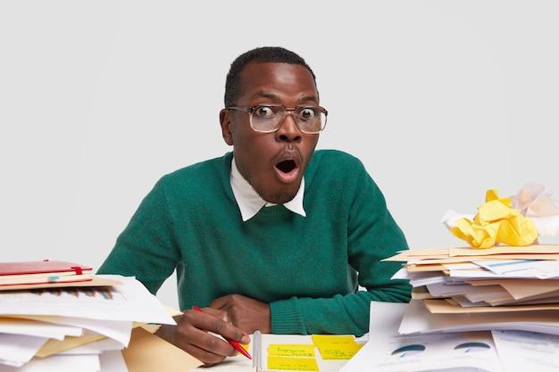 Un jeune comptable stupéfait à la peau noire, garde la mâchoire baissée, réagit à quelque chose de négatif et de choquant