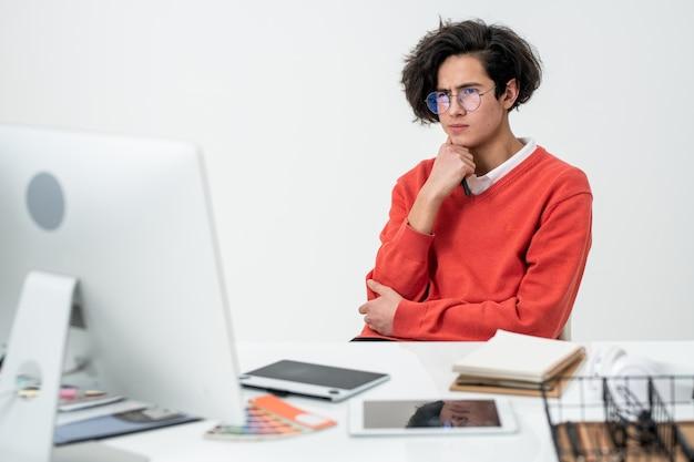 Jeune concepteur web créatif se concentrant sur le travail sur un nouveau projet en ligne assis devant un écran d'ordinateur