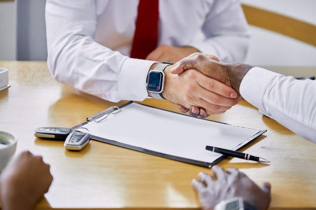 Jeune concessionnaire caucasien donnant la clé au nouveau propriétaire afro-américain et se serrant la main
