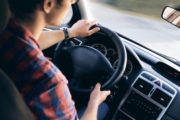 Jeune conducteur dans sa chemise dans une belle voiture moderne en mouvement