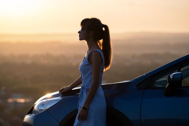 Jeune conductrice se reposant près de sa voiture profitant d'une chaude soirée d'été.