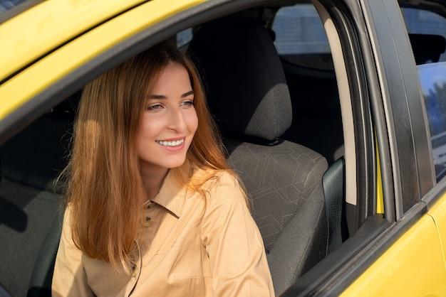 Jeune conductrice souriante regardant par la fenêtre de sa voiture jaune alors qu'elle était assise sur le siège du conducteur