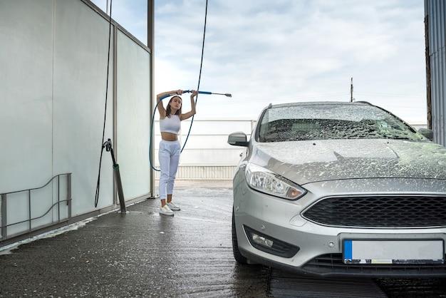 Une jeune conductrice d'un tuyau à haute pression applique de la mousse de savon sur la voiture pour le nettoyer de la saleté au lavage de voiture manuel