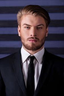 Jeune et confiant. portrait de beau jeune homme en tenue de soirée regardant la caméra en se tenant debout sur fond rayé