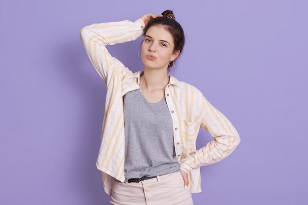 Jeune confiante jeune femme posant à l'intérieur avec des lèvres arrondies, gardant la main sur la tête, montrant le geste du baiser