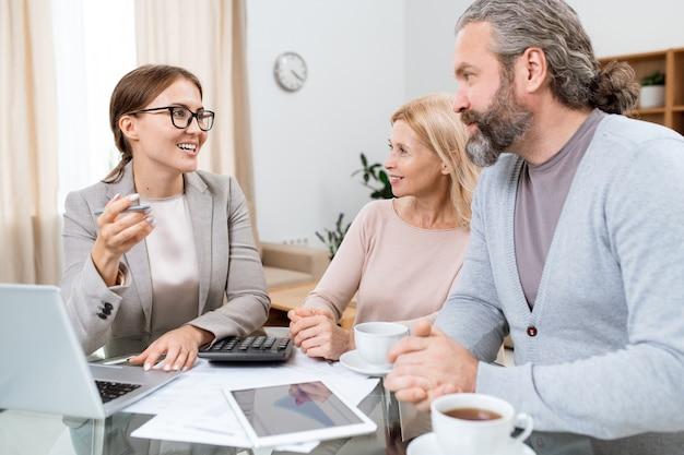 Jeune conseiller financier joyeux ou agent consultant un mari et une femme mûrs sur les possibilités pour les retraités