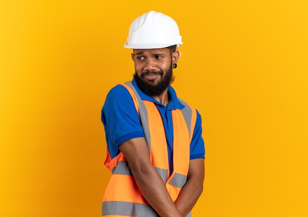 Jeune constructeur agacé en uniforme avec un casque de sécurité regardant le côté isolé sur un mur orange avec espace pour copie