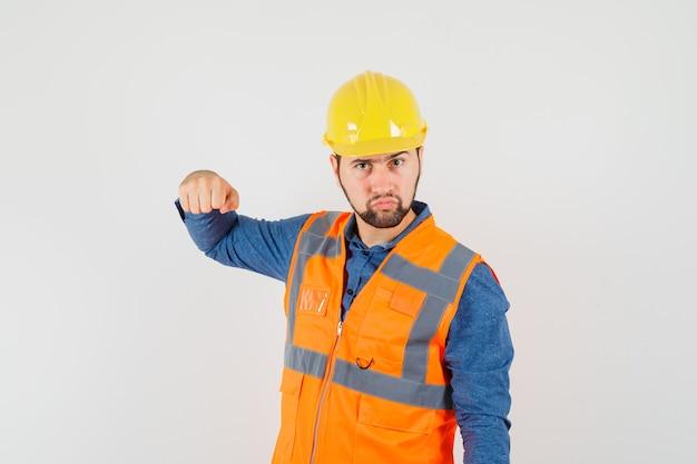 Jeune constructeur en chemise, gilet, casque menaçant avec le poing et regardant grave, vue de face.