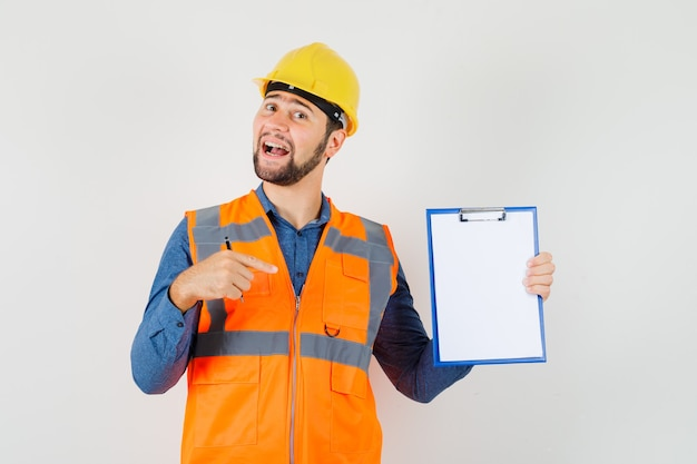 Jeune constructeur en chemise, gilet, casque pointant sur le presse-papiers et à la joyeuse vue de face.