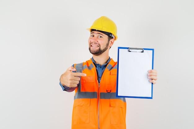 Jeune constructeur en chemise, gilet, casque pointant sur le presse-papiers et regardant gai, vue de face.