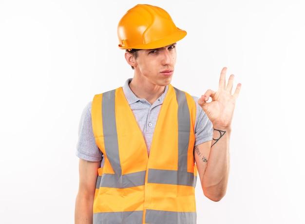 Jeune constructeur confiant en uniforme montrant un geste correct