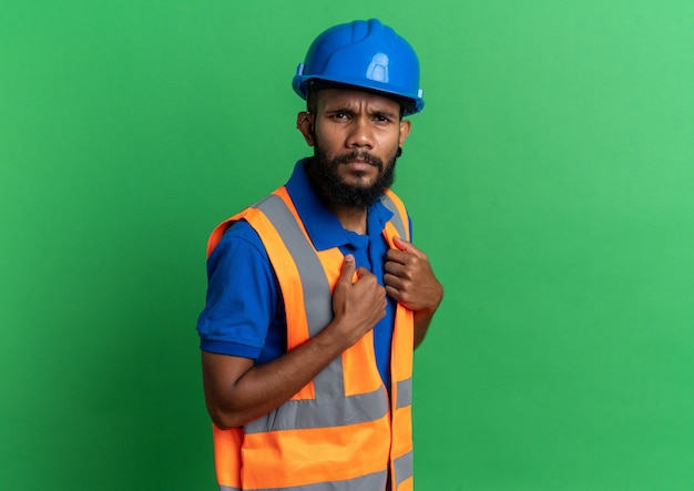 Jeune constructeur désemparé en uniforme avec un casque de sécurité regardant à l'avant isolé sur un mur vert avec espace pour copie