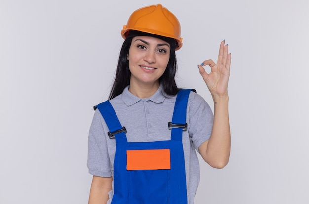 Jeune constructeur femme en uniforme de construction et casque de sécurité à l'avant souriant heureux et positif montrant signe ok debout sur un mur blanc