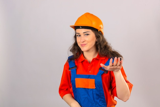 Jeune constructeur femme en uniforme de construction et casque de sécurité demandant de se détendre prendre facilement lever la main tenir calme geste souriant amical sur mur blanc isolé