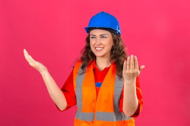Jeune constructeur femme en uniforme de construction et casque de sécurité levant les mains sur le côté dans la consternation et la déception regard confus perplexe ce qui s'est passé sur mur rose isolé