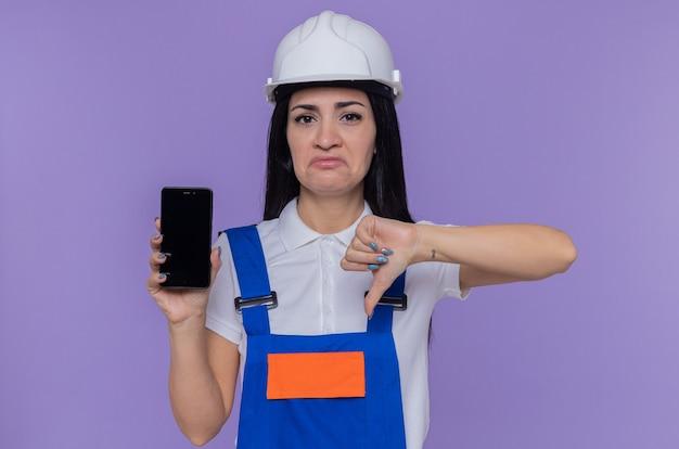 Jeune constructeur femme en uniforme de construction et casque de sécurité montrant smartphone à l'avant d'être mécontent montrant le pouce vers le bas debout sur le mur violet