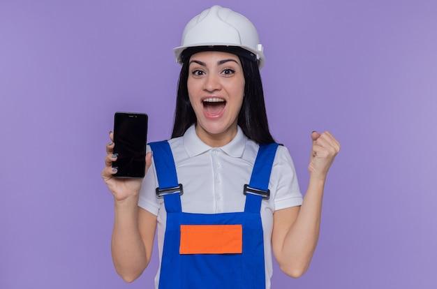 Jeune constructeur femme en uniforme de construction et casque de sécurité montrant smartphone à l'avant poing serré heureux et excité debout sur le mur violet