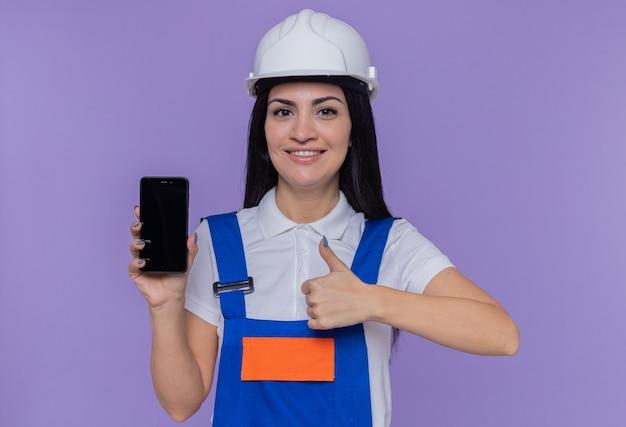 Jeune constructeur femme en uniforme de construction et casque de sécurité montrant smartphone à l'avant souriant confiant montrant le pouce vers le haut debout sur le mur violet