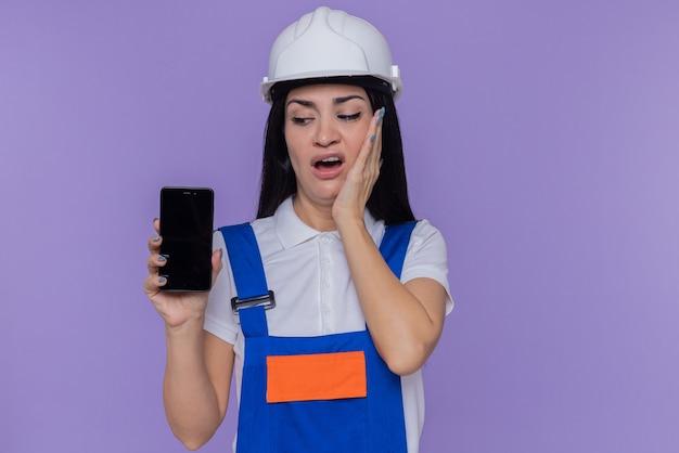 Jeune constructeur femme en uniforme de construction et casque de sécurité montrant smartphone en le regardant confus et très anxieux debout sur le mur violet