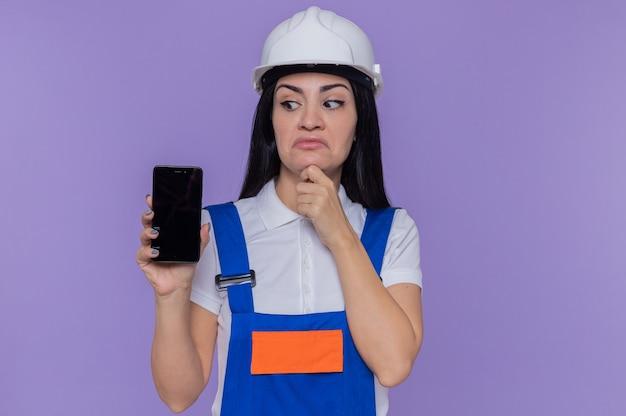 Jeune constructeur femme en uniforme de construction et casque de sécurité montrant smartphone en le regardant avec la main sur le menton avec une expression pensive pensant debout sur le mur violet