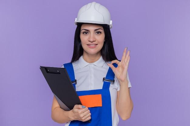 Jeune constructeur femme en uniforme de construction et casque de sécurité tenant le presse-papiers et crayon à l'avant heureux et positif souriant confiant faisant signe ok debout sur le mur violet