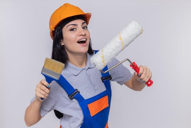 Jeune constructeur femme en uniforme de construction et casque de sécurité tenant le rouleau à peinture et le pinceau à l'avant souriant heureux et positif debout sur un mur blanc