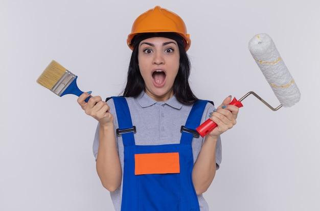 Jeune constructeur femme en uniforme de construction et casque de sécurité tenant un rouleau à peinture et un pinceau à l'avant surpris debout sur un mur blanc