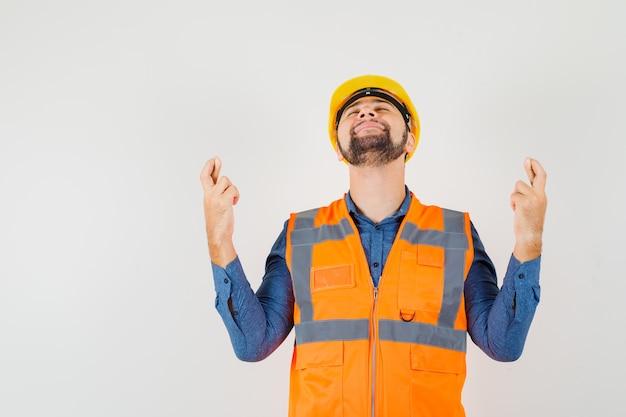 Jeune constructeur gardant les doigts croisés en chemise, gilet, casque et à la recherche de calme. vue de face.