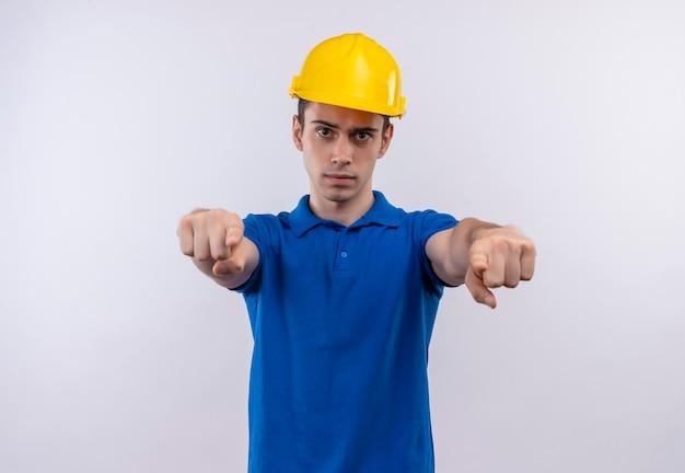 Jeune constructeur homme portant un uniforme de construction et un casque de sécurité pointe sérieusement les doigts à l'avant